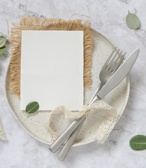 Blank paper card laying on white plate with fork and knife on marble table with eucalyptus branches and vintage ribbons around, top view. card mockup