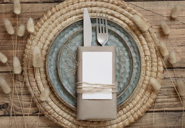 Пустая бумажная карточка на сервировке стола на деревянном столе с богемными украшениями и сушеными растениями вокруг, вид сверху. макет карты места в стиле бохо