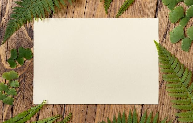 シダの葉の上面図で飾られた木製のテーブルの上の白紙のカード。招待状フラットレイと熱帯のモックアップシーン