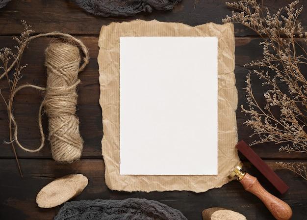 Пустая бумажная карточка на деревянном столе с сушеными цветами и веревкой на коричневом деревянном столе сверху. бохо естественный макет сцены с шаблоном пригласительного билета