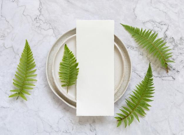 Пустая бумажная карточка на плите на мраморном столе с листьями папоротника вокруг вида сверху. тропический макет сцены с плоской планировкой меню
