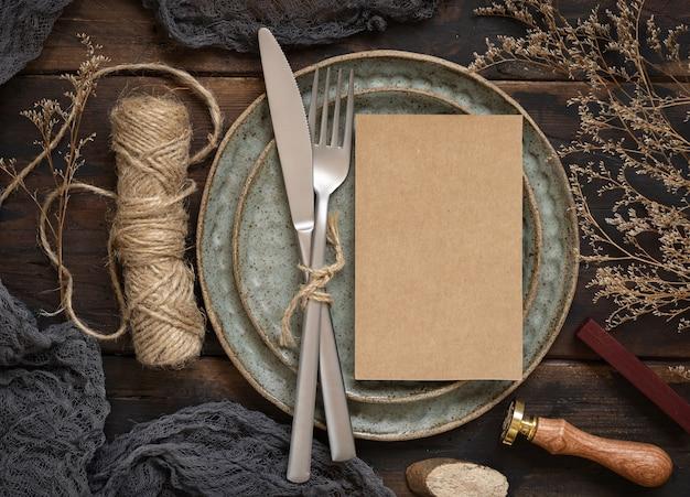 Пустая бумажная карточка на тарелке с вилкой и ножом на деревянном столе с богемным декором вокруг