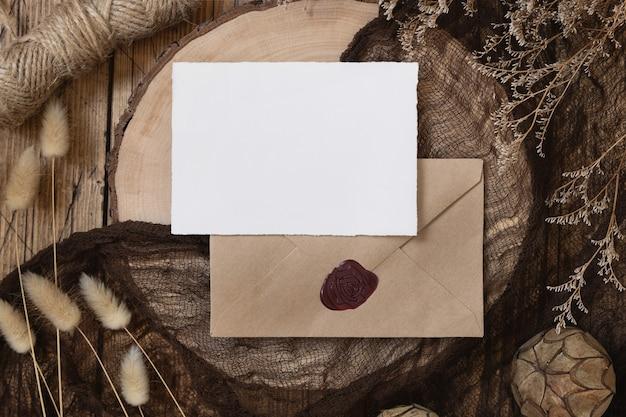 Пустая бумажная карточка на запечатанном конверте и деревянный стол с сушеными растениями, вид сверху, сцена макета в стиле бохо wi