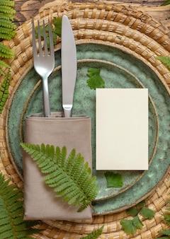 Пустая бумажная карточка на сервировке стола, украшенной листьями папоротника на взгляд сверху деревянного стола. тропический макет сцены с плоской планировкой карты места