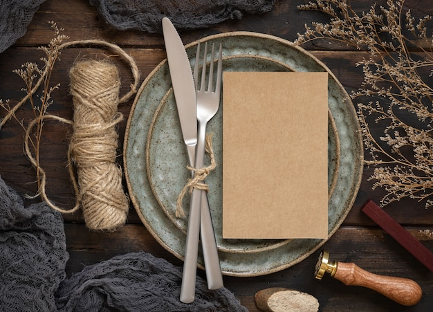 Blank paper card on plate with fork and knife on wooden table with bohemian decoration around