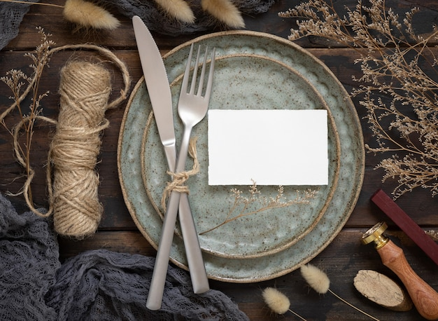 Blank paper card on plate with fork and knife on wooden table with bohemian decoration