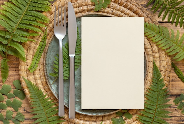 Blank paper card on a plate with knife and fork decorated with fern leaves on wooden table top view. tropical mock-up scene with invitation card flat lay