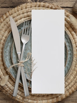 Blank paper card on plates with dried plants
