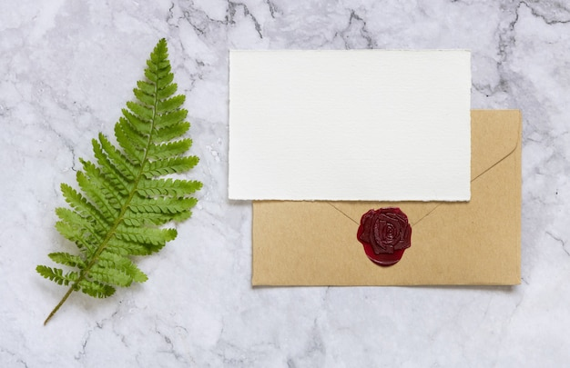 Blank paper card and sealed envelope decorated with fern leaves on white marble table top view. tropical mock-up scene with greeting card flat lay