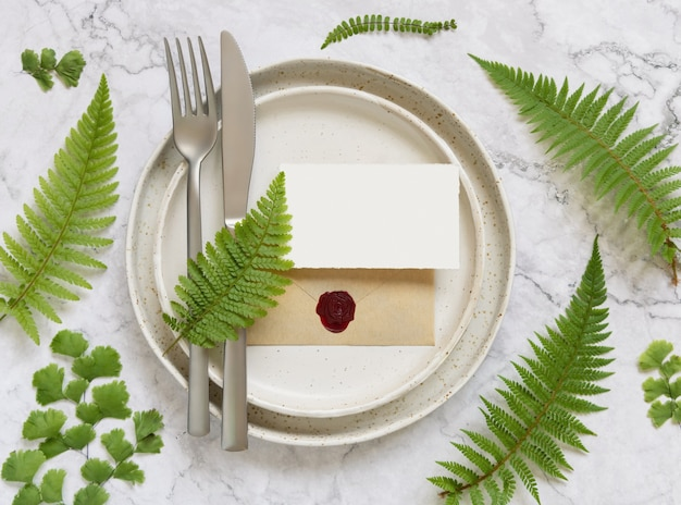 Blank paper card and sealed envelope on table setting decorated with fern leaves on white marble table top view. tropical mock-up scene with place card flat lay