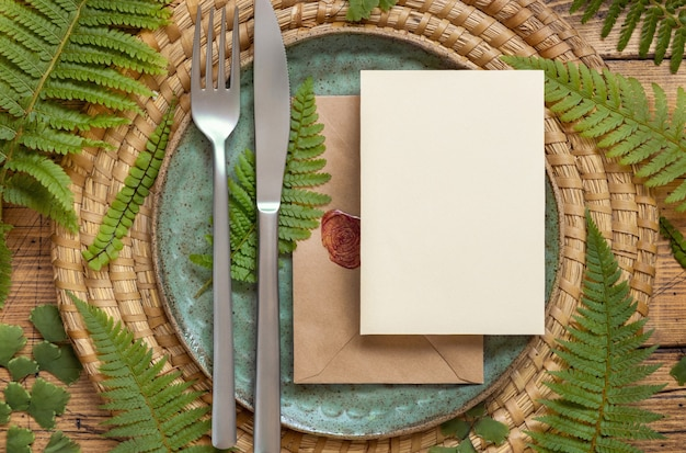 Blank paper card and sealed envelope on table setting decorated with fern leaves on wooden table top view. tropical mock-up scene with invitation card flat lay