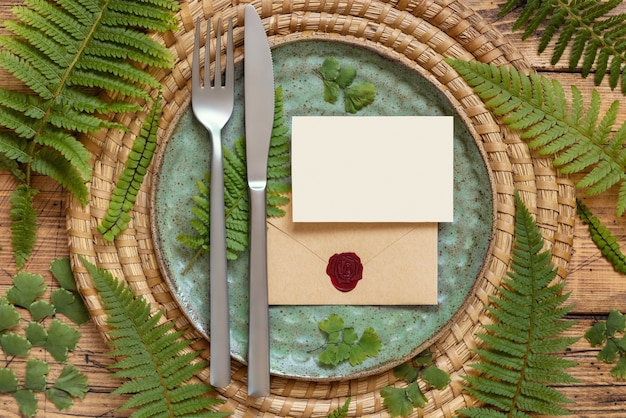 Blank paper card and sealed envelope on table setting decorated with fern leaves on wooden table top view. tropical mock-up scene with wedding card flat lay