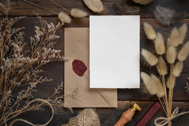 Blank paper card on sealed envelope and wooden table with dried plants top view boho mockup scene wi