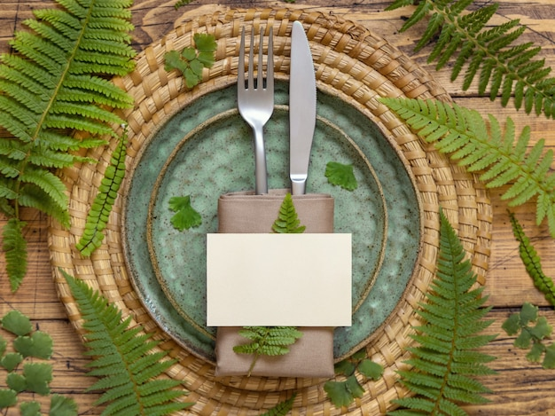 Blank paper card on table setting decorated with fern leaves on wooden table top view. tropical mock-up scene with place card flat lay