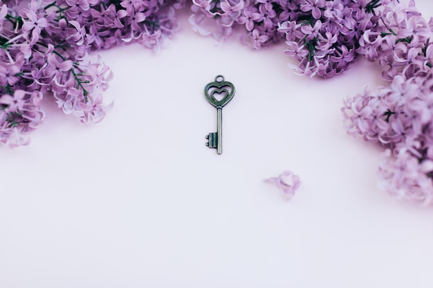 Blank paper card with lilac flowers and vintage key on pink background. space for text. flat lay style.