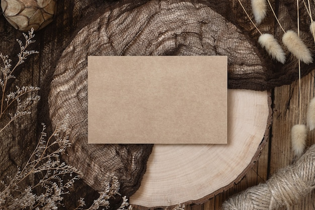 Blank paper card on a wooden table with dried plants around, top view. boho mock-up scene with invitation card template