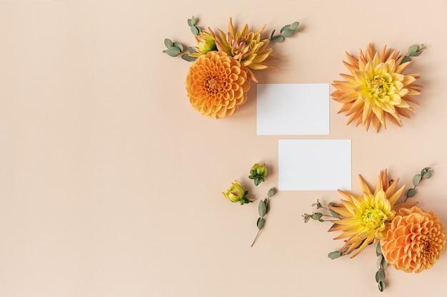 白紙のカード。美しい生姜ダリアの花のつぼみとユーカリの枝で作られたフレーム。フラットレイ