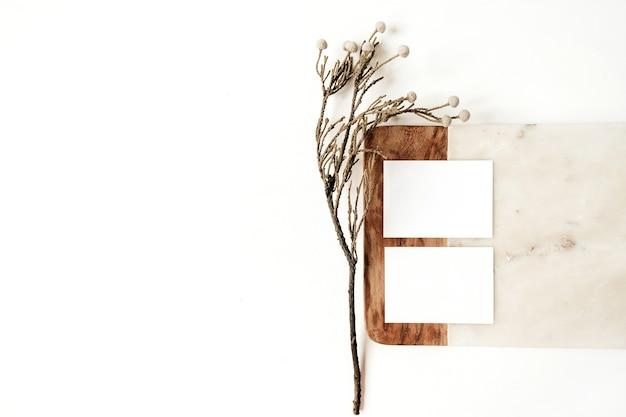 白のフローラルブランチと大理石のボード上の空白の紙カード