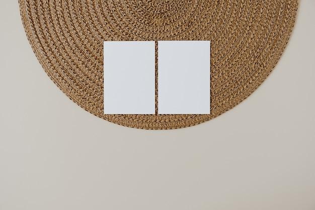 コピースペースとベージュの籐ナプキンが付いている白紙のカード。最小限のビジネスブランドテンプレート。フラットレイ、上面図