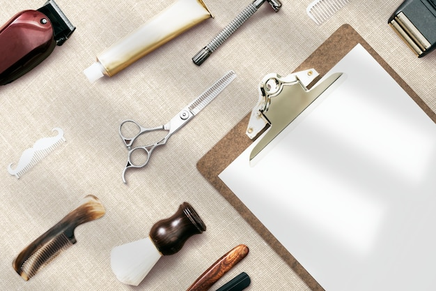 Blank paper clipboard flat lay with barber tools job and career concept
