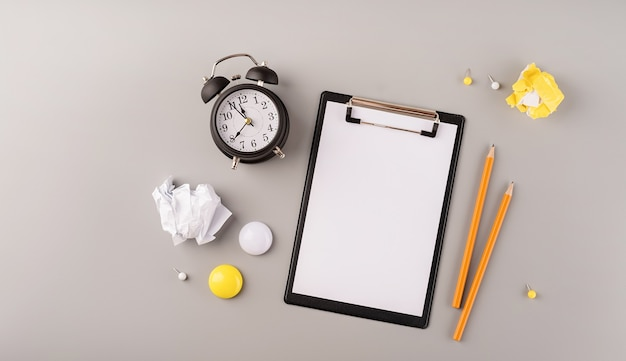 Blank paper on clipboard white alarm clock and stationery top view on gray background