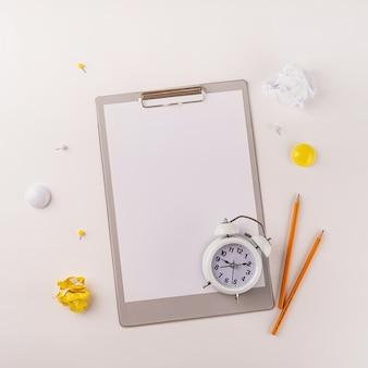 Blank paper on clipboard white alarm clock and stationery top view on white background