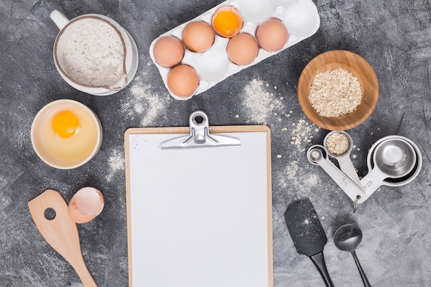 Blank paper on clipboard with baking ingredients over concrete backdrop