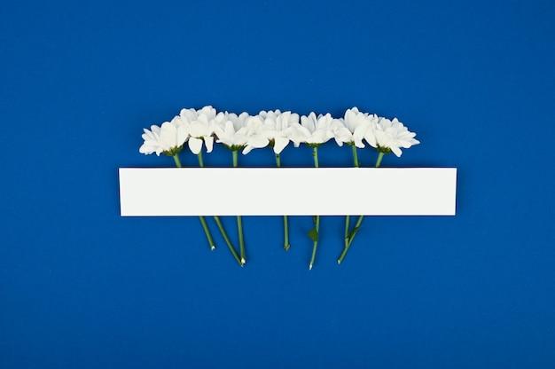 空白の紙のコピースペース。花のあるフレーム。白い菊。青色の背景。シンプルな花束。グリーティングカード