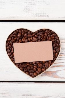 Blank paper for copyspace over coffee heart. flat lay roasted coffee beans arranged in a heart shape.