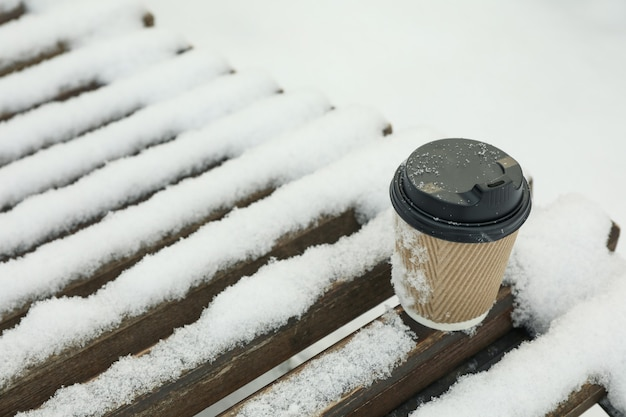 Blank paper cup on bench outdoor in winter