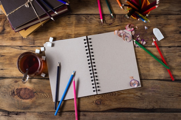 Blank paper, cup tea and colorful pencils on old wooden table. flat lay, top view