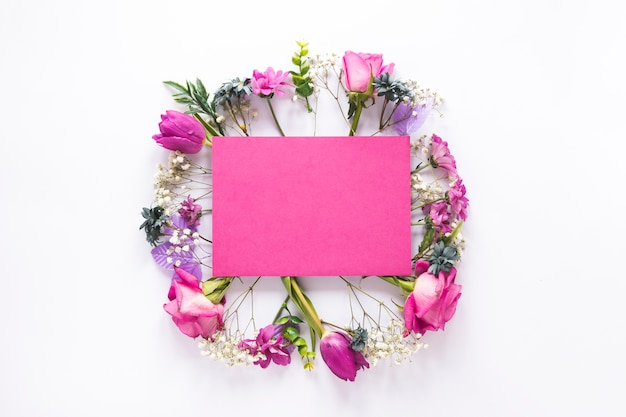 Blank paper on different flowers on table