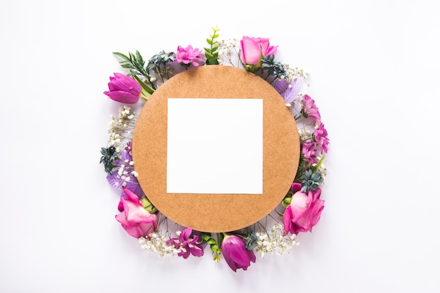 Blank paper on different flowers on white table