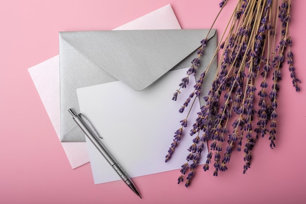 Blank paper in envelope and lavender flowers on pink background. simple wedding arrangement. top view