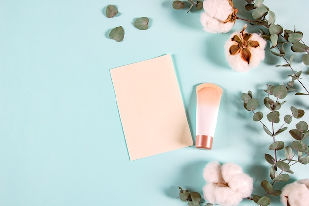 Blank paper envelopes with eucalyptus leaves, cream jar and cotton flowers on light background