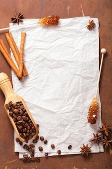 コーヒーとスパイスと木製のテーブルの上のレシピの白紙