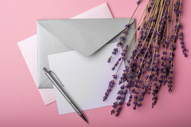 Чистый лист бумаги в цветках конверта и лаванды на розовом фоне. простая свадебная композиция. вид сверху