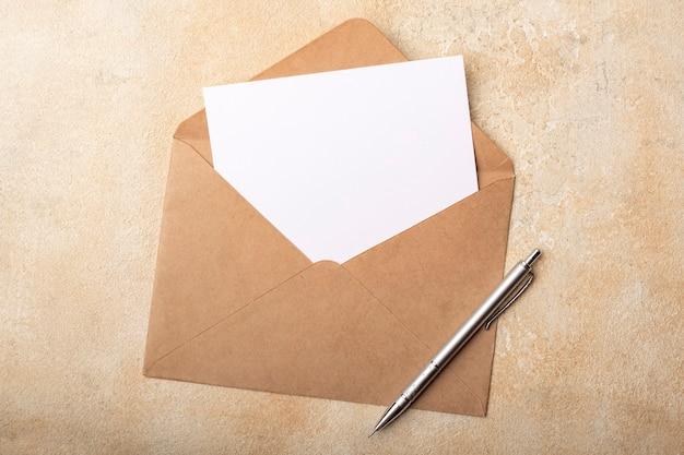 밝은 배경에 kraft 봉투에 빈 종이. 서명을위한 깨끗한 엽서. 평면도