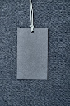 Blank paper label on blue linen clothes table