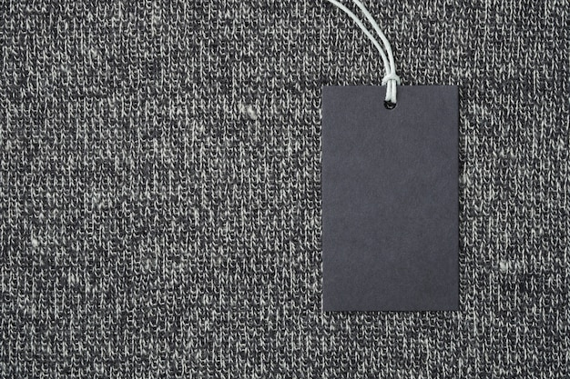 Blank paper label or tag on knitted wool clothes background