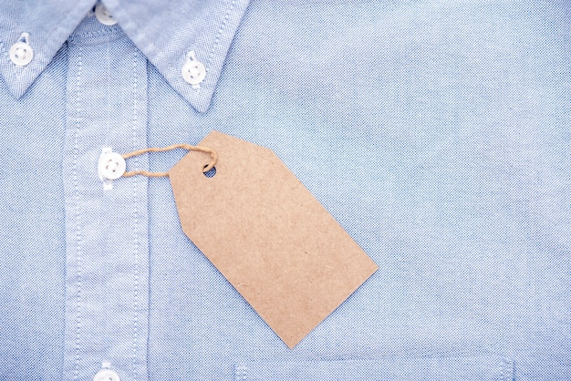 Blank paper label or tag on top of blue shirt, space for text