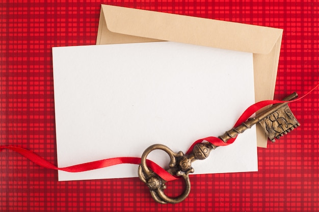 Blank paper note, craft envelope on red