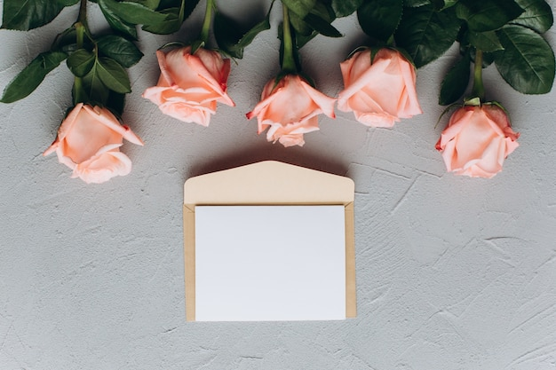 Blank paper note with envelope, gifts and pink rose