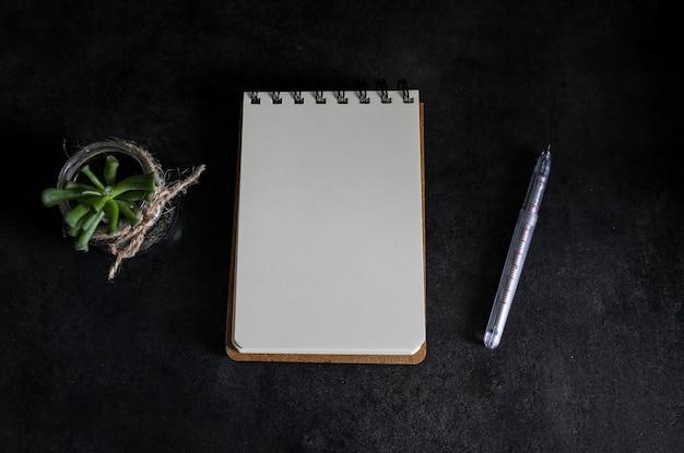 Тетрадь чистого листа бумаги на сером столе.