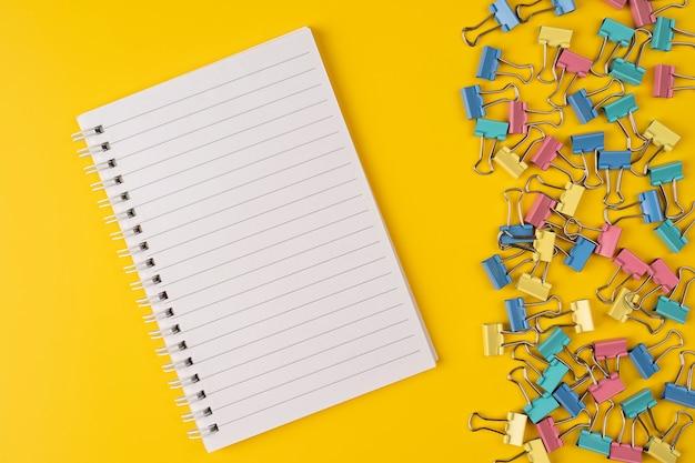 黄色の背景にカラーペーパークリップと空白の紙のノート。フラットレイ。上面図。最小限のビュー