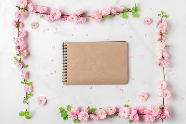 白い大理石の背景にピンクの花と白紙のノート。女性の日、母の日、バレンタインデー、結婚式のコンセプト。フラットレイ、コピースペース付きの上面図