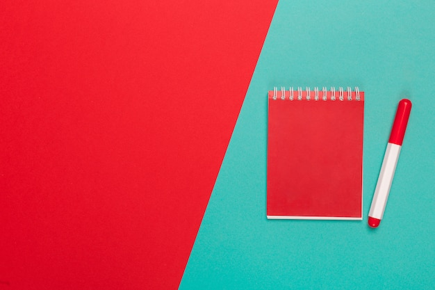 Blank paper notepad on bright bicolor background for your design, top view