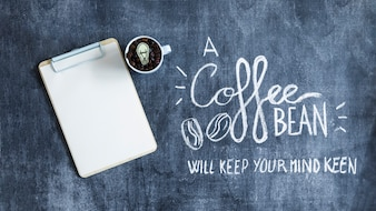 Blank paper on clipboard with coffee beans mug and text on blackboard