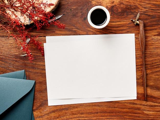書道ペンとインクで木製の背景の空白の紙。上からの眺め。