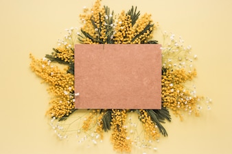 Чистый лист бумаги на желтых цветочных ветках